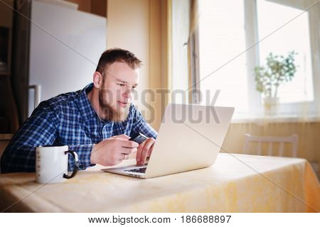 Man Using Laptop And Smart Phone At The Table In Office Against The Window
