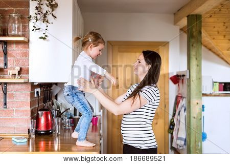 Beautiful young mother at home and her cute little daughter jumping from kitchen countertop into her arms.