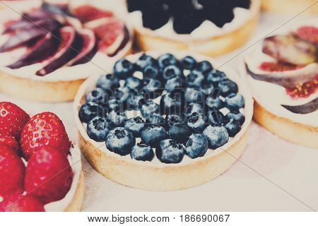 Blueberry tarts dessert tray assorted. Closeup of beautiful delicious pastry sweets. French Bakery catering. Filtered, shallow depth of field
