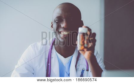 Close-up of male doctor giving jar of pills to patient