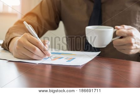 Businessman analyzing graph document and holding coffee in office.