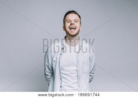 Standing smiling young man with beard in a white shirt mocking and looking right at the camera. Attractive guy making funny face holding hands behind. Close up. Isolated