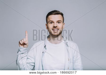 Portrait of handsome confident man pointing up with one forefinger standing on white background. He is looking at the camera as in process of saying something. Close up. Isolated