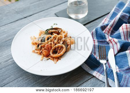 Restaurant food. Seafood tomato pasta with calamari rings and mussels on white round plate. Diet and healthy meals, candid image of served table