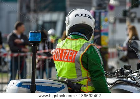 BERLIN - APRIL 03 2016: The annual Berlin Half Marathon. Before the start of the race. A police officer on a motorcycle escort.