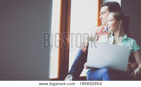 Couple moving in house sitting on the windowsill with laptop