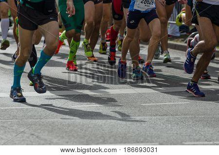 BERLIN - APRIL 03 2016: The annual Berlin Half Marathon. Race through the city streets. Legs of athletes close-up.