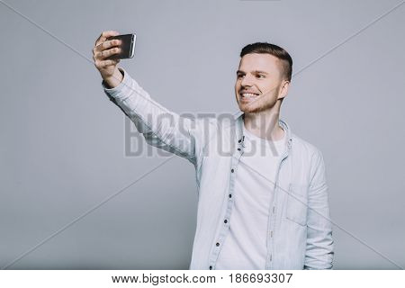 Attractive cheerful guy in stylish casual wear standing with mobile phone and trying to make a good selfie picture. Close up. Isolated
