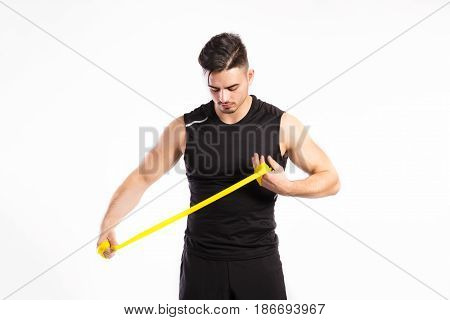 Young handsome fitness man in black sleeveless shirt working out with rubber band. Studio shot on white background.