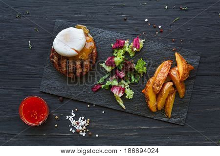 Grilled beef steak with poached egg and roasted potato wedges on black wood table background, top view. Juicy meat with rosemary, lettuce and cutlery on stone board. restaurant food