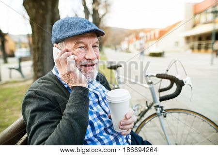 Handsome senior man with bicycle in town park sitting on bench, holding coffee and smart phone, making phone call. Sunny spring day.