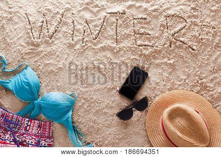 The word Winter written in a sandy tropical beach