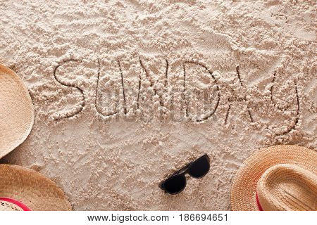 The word Sunday written in a sandy tropical beach