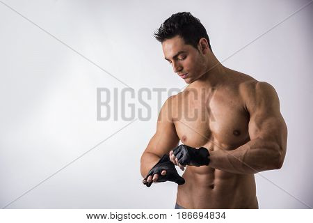 Half Body Shot of a Topless Muscled Man Wearing Black Gloves for Workout on Light Background.