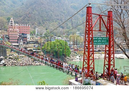 INDIA, LAXMAN JHULA - APRIL 13, 2017: People walking on the suspension bridge at the river Ganges in Laxman Jhula on 13th april 2017