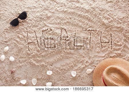 The word Health written in a sandy tropical beach