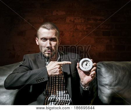 a stern man in a business suit showing on the clock against a brick wall