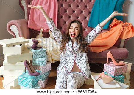 Image of happy young lady sitting on floor near sofa indoors choosing shoes. Eyes closed.