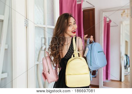 Picture of young happy woman standing in clothes shop indoors holding three backpacks. Looking at camera.