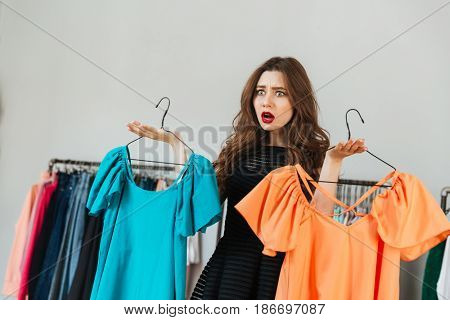 Image of confused young woman standing in clothes shop indoors choosing between two dresses. Looking aside.
