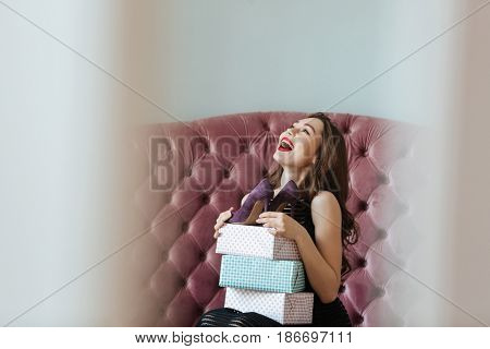 Picture of happy young lady sitting on sofa indoors choosing shoes. Looking aside.