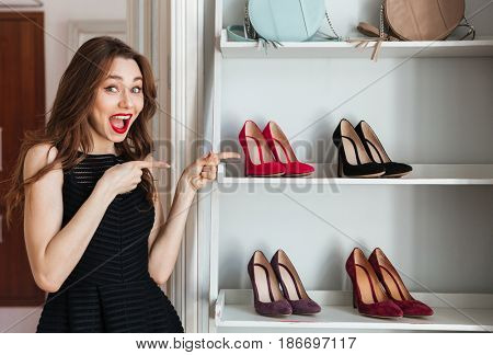 Image of happy young woman standing in clothes shop indoors choosing shoes. Looking at camera and pointing.