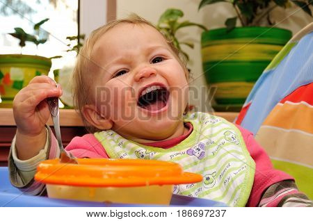 smiling baby eating food alone on kitchen