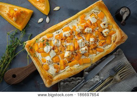 Tart with pumpkin feta ricotta cheese and thyme on a dark concrete background. Top view. Selective focus.