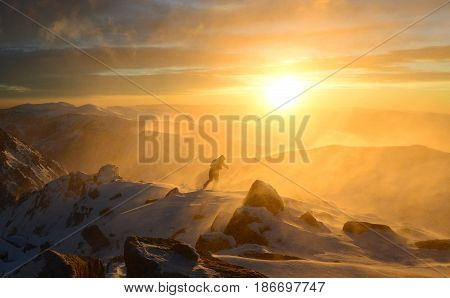 A man fights with bad weather in the winter mountains