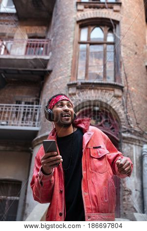 Portrait of a happy young afro american man in headband enjoying listening to music with headphones and smartphone outdoors on a street