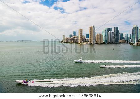 Miami. USA-February 19 2017: skyscrapers with blue cloudy skywhite boat sailing next to Miami downtown Aerial view