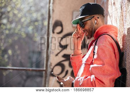 Portrait of a handsome hipster afro american man in sunglasses listening music with mobile phone and earphones while leaning on a street wall