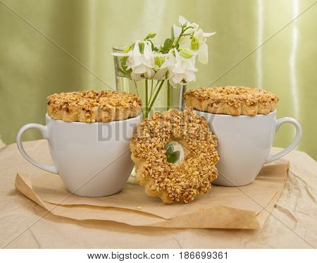 white Cup with milk, with biscuits and white flowers