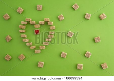 Brown Sugar cubes shaped as heart on greenery background. Top view. Diet unhealty sweet addiction concept