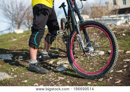 The rider in full protective equipment on the mtb bike resting stands on a green grass