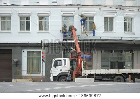 Moscow, Russia - May, 8, 2017: Workers repair the facade of building in Moscow