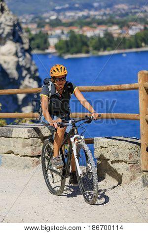 Mountain biking woman at sunrise over Lake Garda on path Sentiero della Ponale, Riva del Garda, Italy