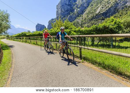 Mountain biking woman and young girl over Lake Garda.