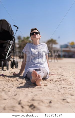 Young mother with sunglasses relaxing on beach with baby stroller outdoor