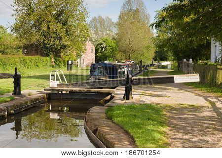 A narrowboat being raised in locks on the Shropshire Union canal in England UK