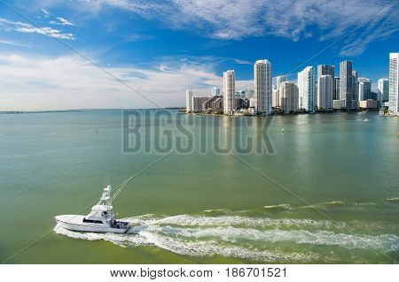 Miami skyscrapers white luxury yacht boat sailing next to Miami downtown Aerial view