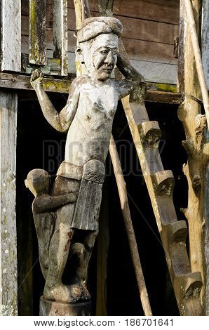 Indonesia Traditional Dayak tribal culture. Totem in front of Dayak house - long house. East Kalimantan Borneo.