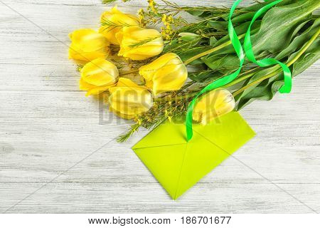 Bouquet of beautiful flowers and envelope on light wooden background