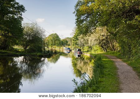 An idyllic view of the 200 year old Shropshire Union canal in England with traditional British narrowboats moored up on the bank
