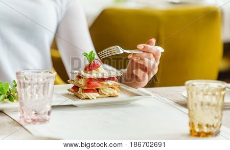 woman eating dessert with strawberries