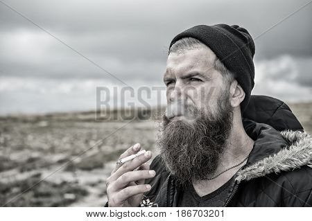 bearded hipster with long beard smoking cigarette in hat on natural background bad habit and addiction lifestyle
