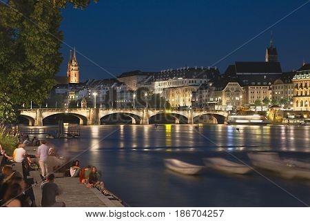 BASEL, SWITZERLAND - JULY 7, 2017: Night scene of Basel in long exposure shot with people enjoying the summer atmosphere by the river, slightly motion blurred as they casually move around