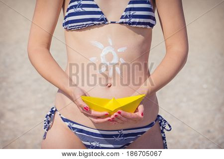 Female hands holding paper boat on the sandy beach background