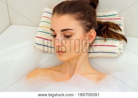Portrait of a beautiful girl with dark hair that is in the water in the bathroom and lowered her eyes down close-up