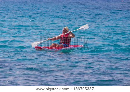 Portrait of man in hat paddles a red kayak in the ocean. Tourism and sport concepts